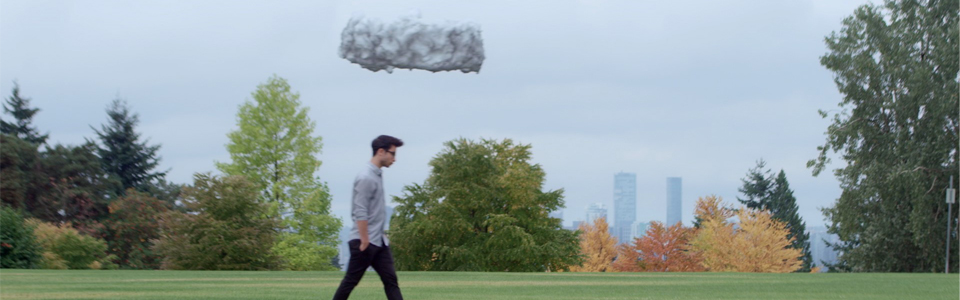 a drone disguised as a cloud hovers directly over the head of a young person walking through the park