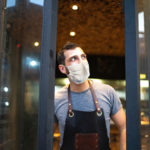 Small business owner closing front door with face mask